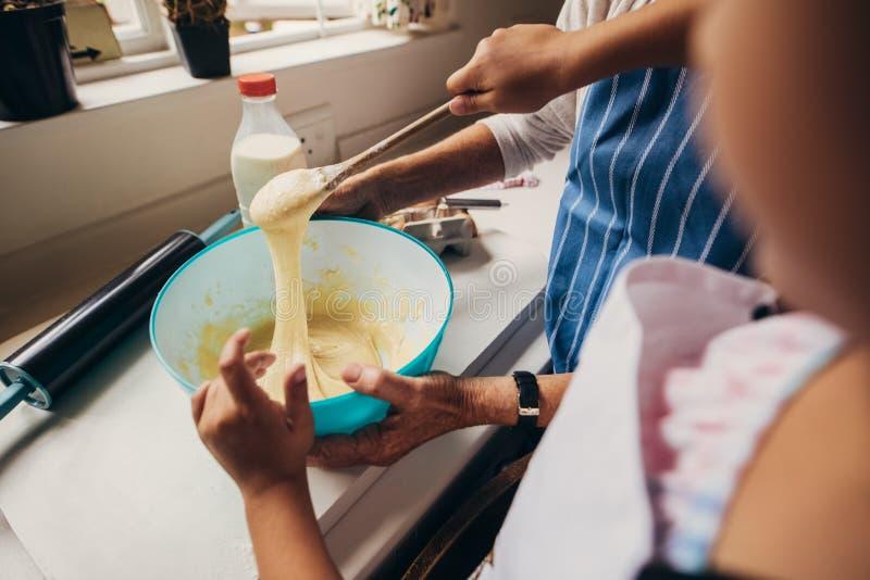 Dwa kobiety robi ciastu naleśnikowemu dla torta obrazy royalty free
