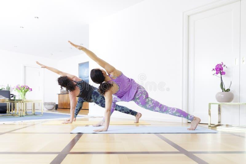 Dwa kobiety robi joga w domu zdjęcia royalty free