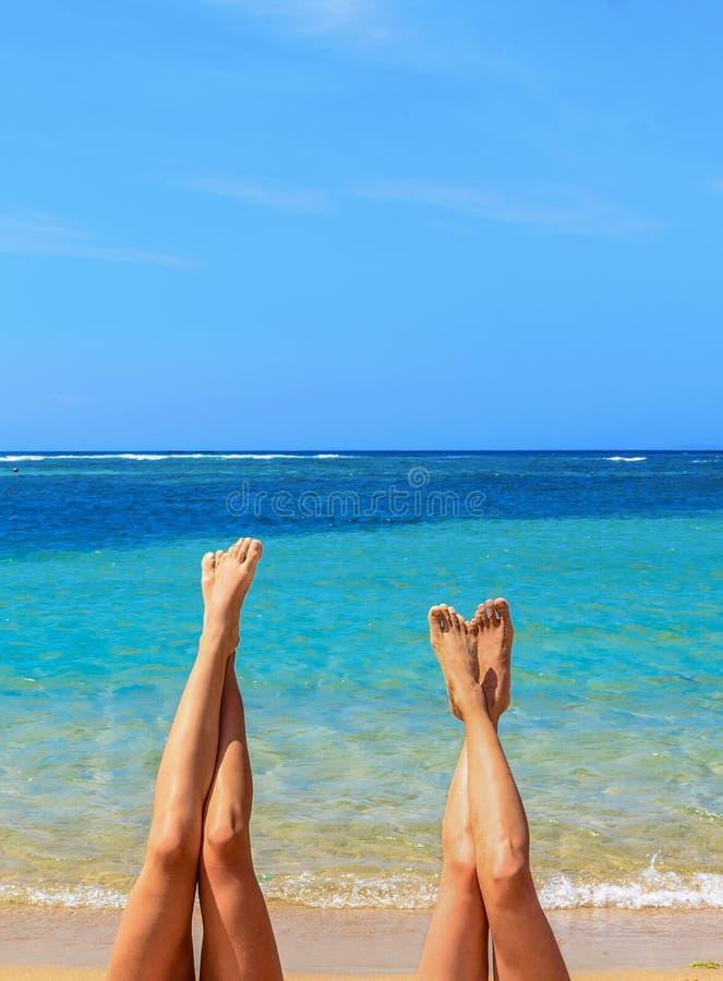 Dwa kobiety stawia ich cieki w górę plaży przy - tropikalny wakacje, lata pojęcia wizerunek zdjęcia stock