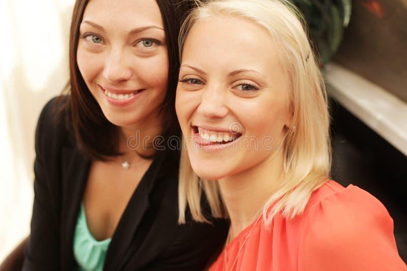 Dwa kobiety szepcze i ono uśmiecha się obrazy stock