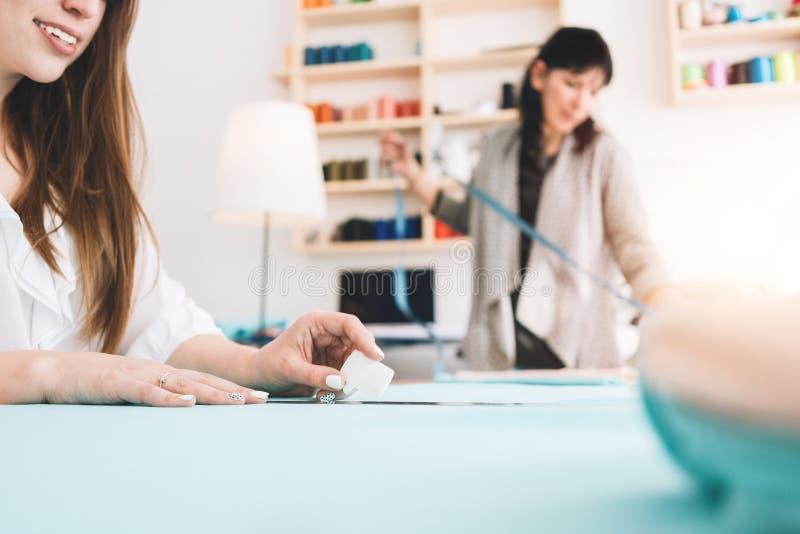 Dwa kobiety tworzą projektant odzież w szwalnym studiu Krawcowa pracuje z płótnem w sala wystawowej obraz royalty free