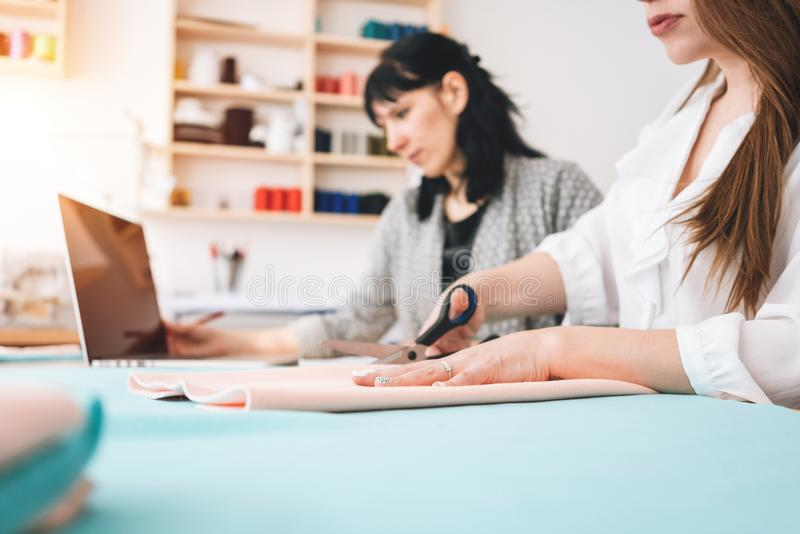 Dwa kobiety tworzą projektant odzież w szwalnym studiu Krawcowa pracuje z płótnem w sala wystawowej zdjęcia stock