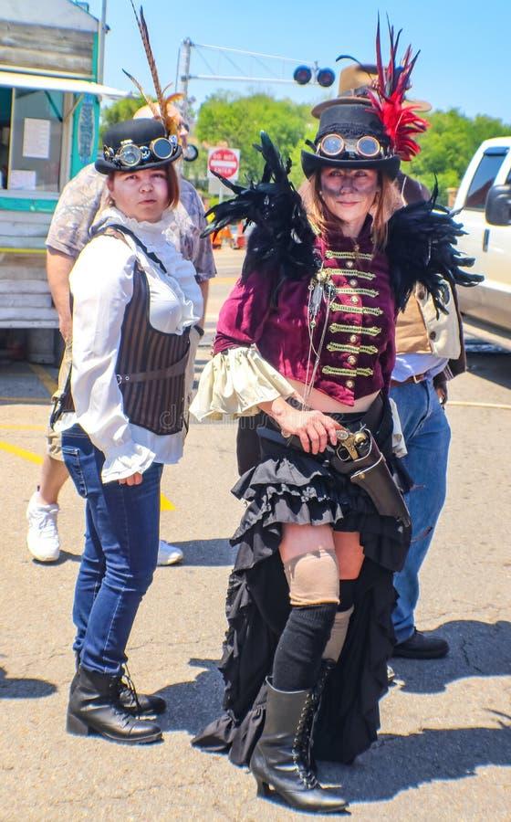 Dwa kobiety ubierali w Steampunk kostiumach z kapeluszami i gogle outdoors z budynkami ciężarówka i mężczyzna - selekcyjna ostroś obraz stock