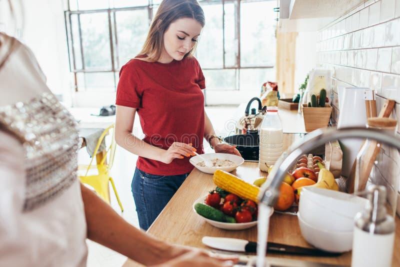 Dwa kobiety w kuchennych kucharstwa i domycia naczyniach obraz stock