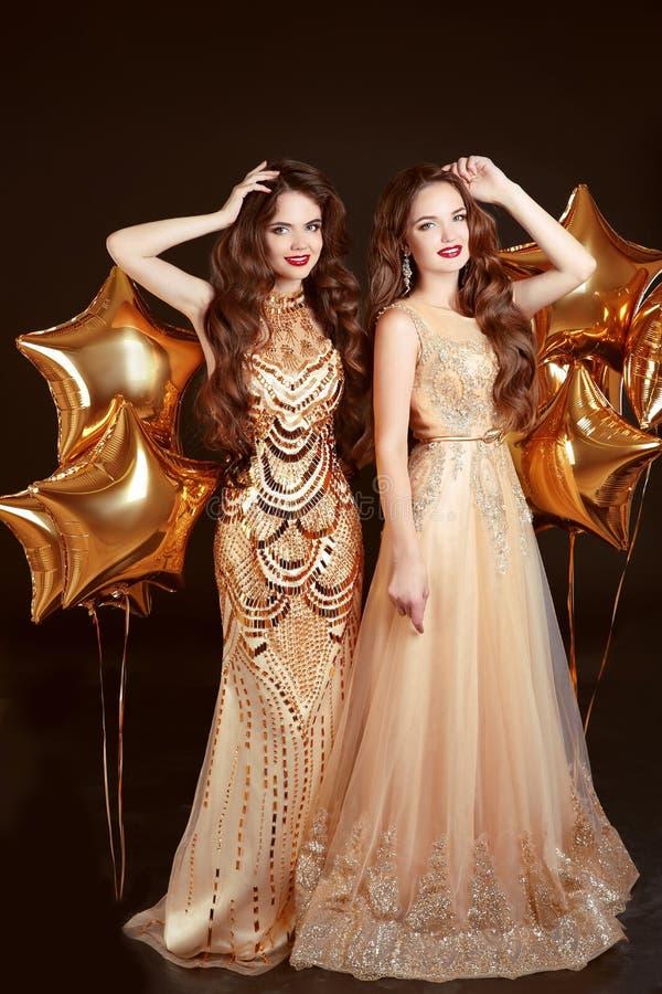 Dwa kobiety w mody sukni, partyjny świętowanie Brunetka bliźniaków gi zdjęcia stock