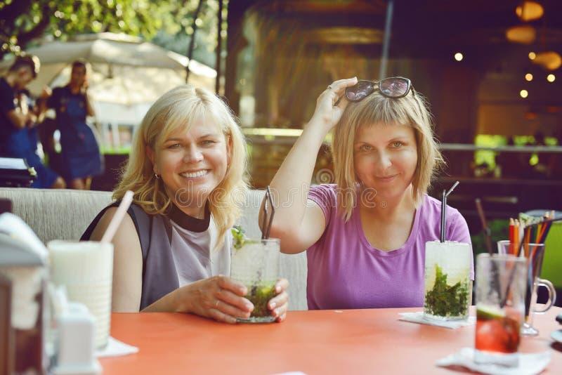 Dwa kobiety w plenerowej kawiarni obrazy stock
