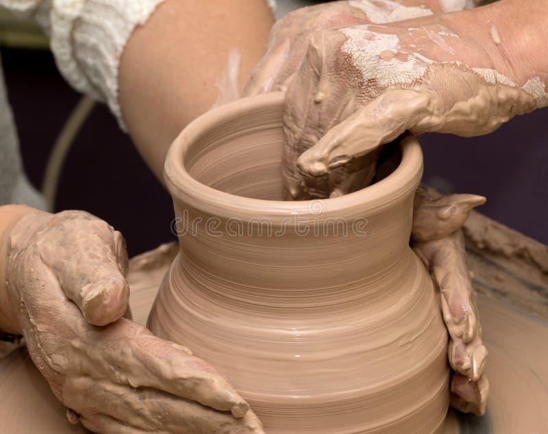 Dwa kobiety w trakcie robić glinianej wazie na ceramicznym kole obraz stock