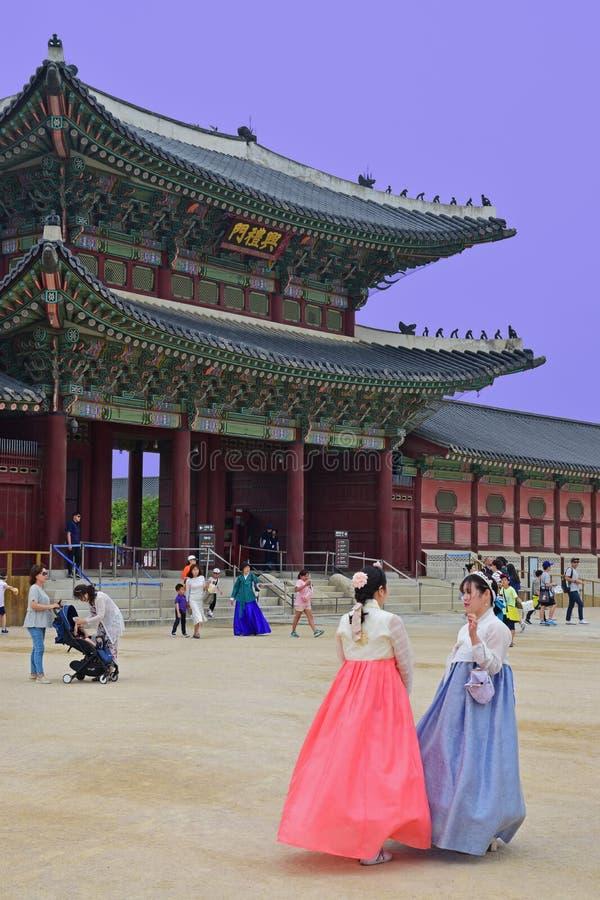 Dwa kobiety w uderzać jaskrawego colour koreańczyka Hanbok stoi rozmowę przed Gyeongbokgung pałac i ma obrazy royalty free