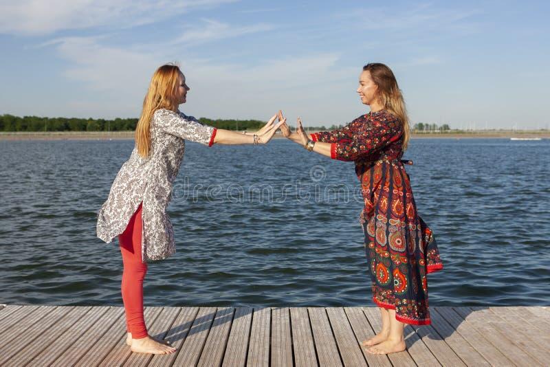 Dwa kobiety ?wiczy w parku M?oda pi?kna kobieta robi ?wiczeniom wp?lnie outdoors fotografia stock