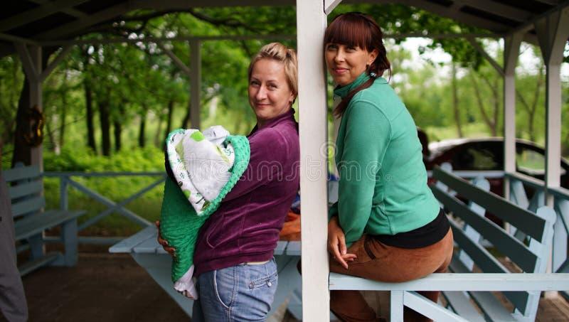 Dwa kobiety z dzieckiem w pieluszce w pawilonie obraz stock