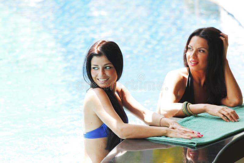 Dwa kobiety z koktajlami w pływackim basenie obrazy royalty free
