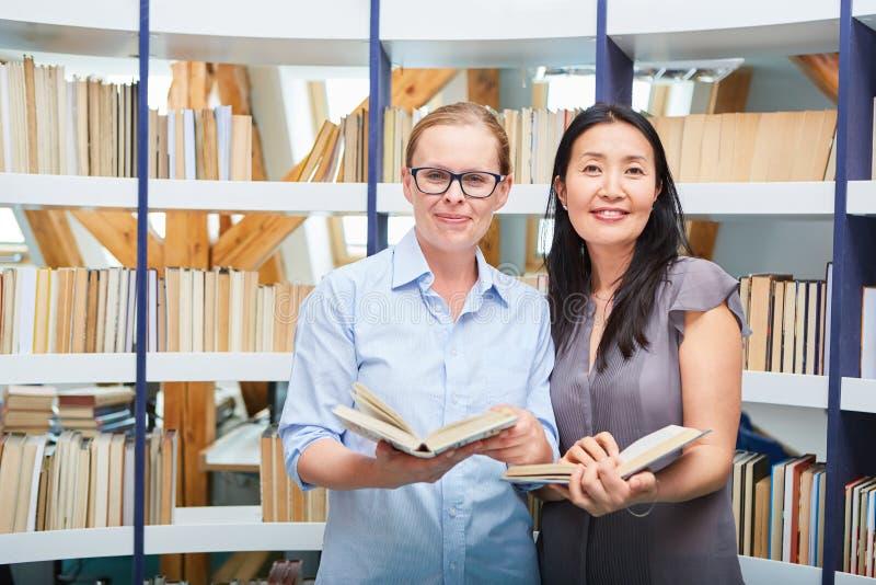 Dwa kobiety z książką jako czytelnik w bibliotece zdjęcie stock