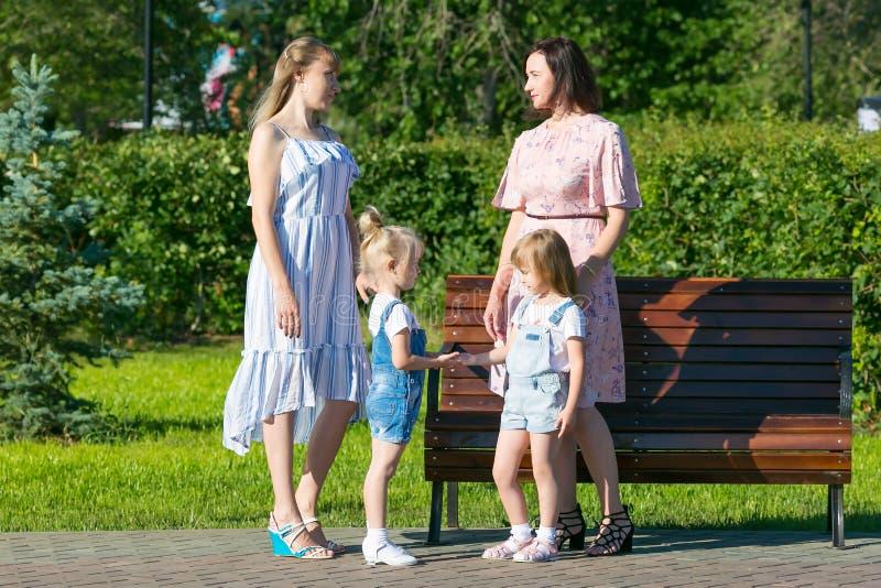Dwa kobiety z młodymi dziećmi na ulicie zdjęcie stock