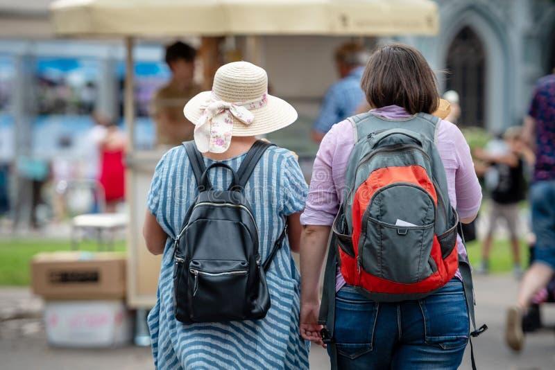 Dwa kobiety z plecakami iść wokoło miasta widok z powrotem zdjęcia stock