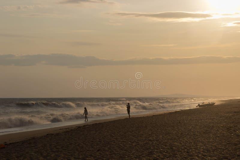 Dwa kochanka chodzi na złotej plaży światłami zmierzch blisko starej łodzi obrazy stock