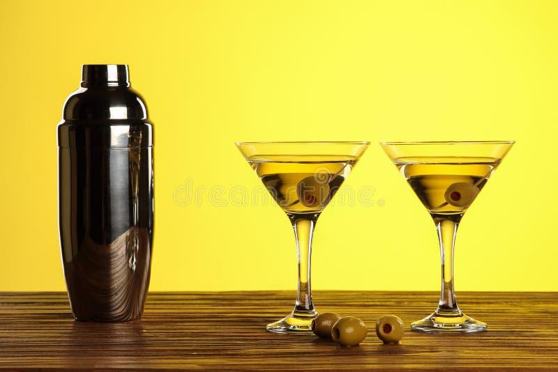 Dwa koktajlu w Martini szkłach z zielonymi oliwkami i potrząsaczem na drewnianej powierzchni przeciw żółtemu tłu z kopii przestrz obraz stock