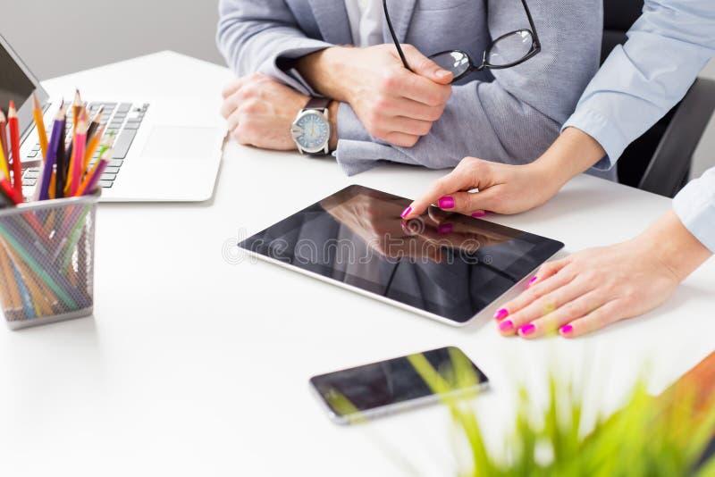 Dwa kolegi patrzeje pastylka komputer przy pracą zdjęcie stock