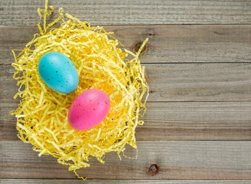 Dwa kolorowego cętkowanego Wielkanocnego jajka w żółtej Wielkanocnej trawie na drewnianym tle zdjęcie royalty free
