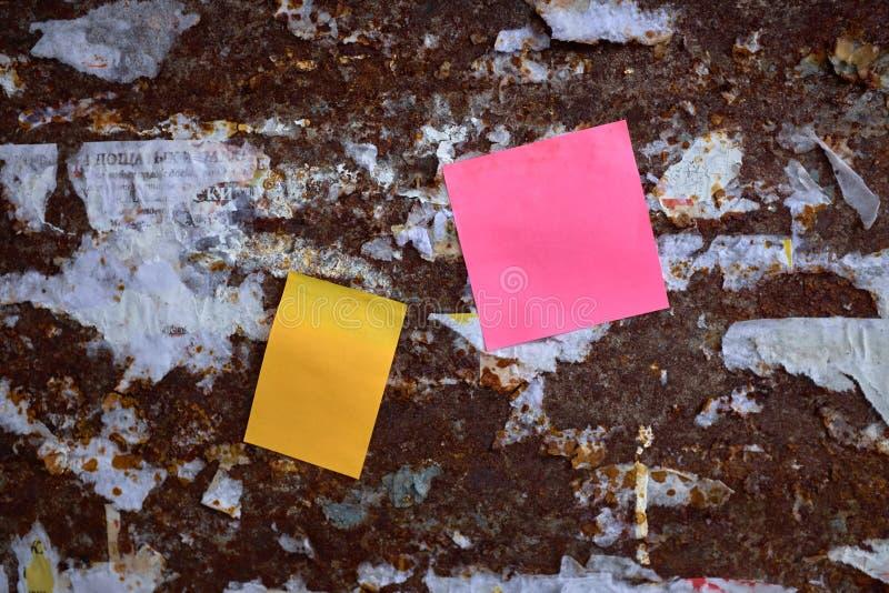 Dwa koloru pusty papier na rdzewiejącej stali ścianie zdjęcie stock