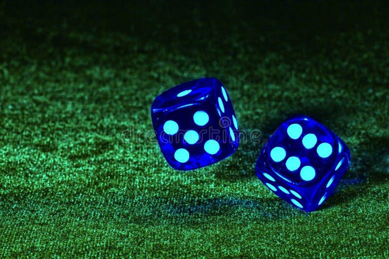 Dwa kostka do gry wirują nad stołowym płótnem obrazy royalty free