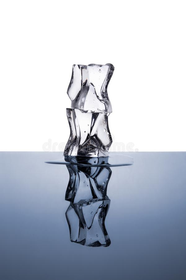 Dwa kostki lodu z wodnymi kroplami odizolowywać na białym i błękitnym zdjęcia royalty free