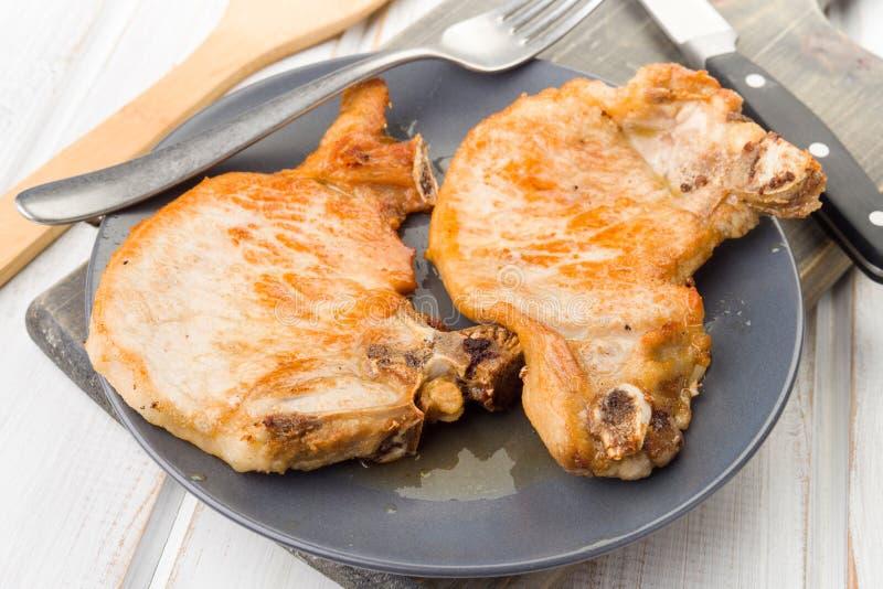 Dwa kotlecika piec wieprzowinę na talerzu, na drewnie zdjęcie royalty free