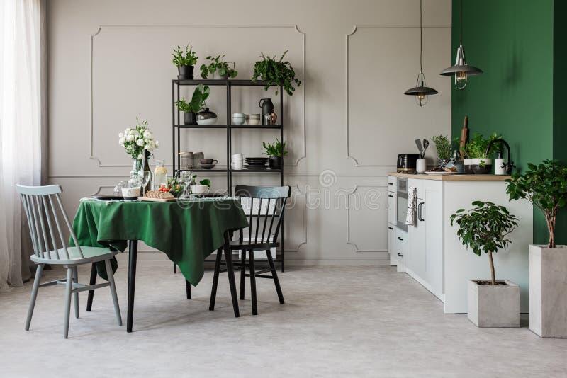 Dwa krzesła przy round stołu setem dla śniadania w rówieśniku otwierają plan kuchnię fotografia stock