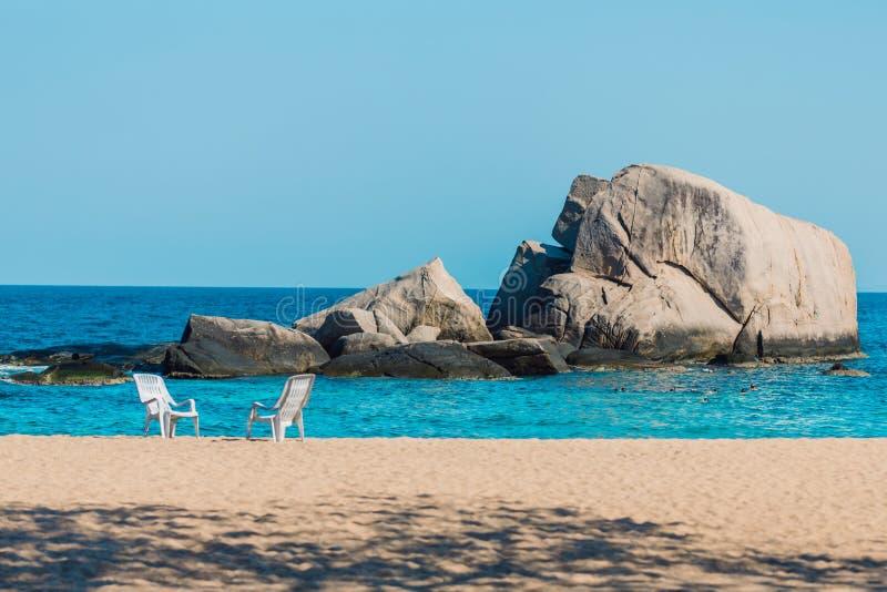 Dwa krzeseł stojak na pustym piaskowatym piasku Opróżnia plażowego i błękitnego morze z skałami w tle b??kitne niebo reszta 2 wak fotografia stock