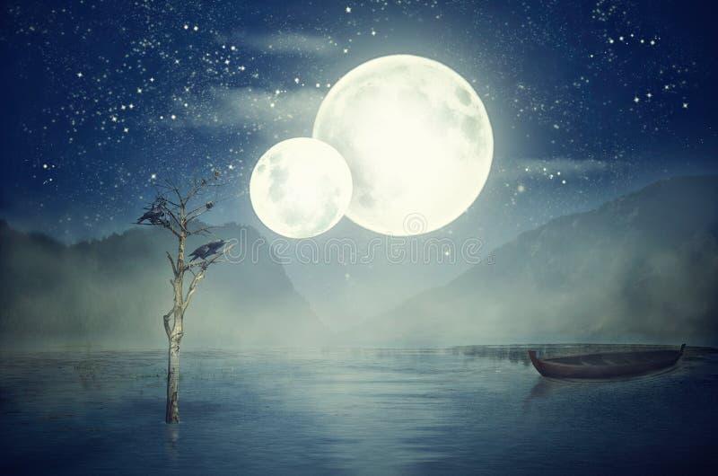 Dwa księżyc na niebie nad jeziorem przy mglistą nocą obrazy royalty free