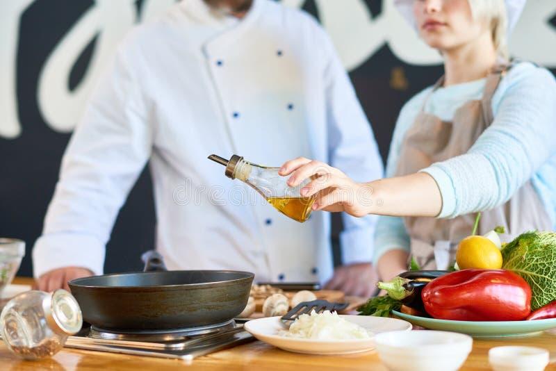 Dwa kucharza Dodaje oliwa z oliwek naczynia zakończenie up zdjęcia stock