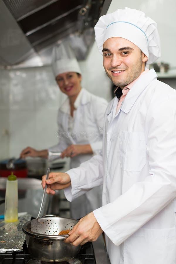 Dwa kucharza przy restauracyjną kuchnią obrazy stock
