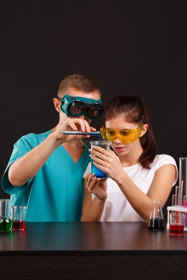 Dwa laboranckiego technika w mundurze nalewają błękitnego ciecz od małej kolby w szklanego pomiarowego szkło zdjęcie royalty free