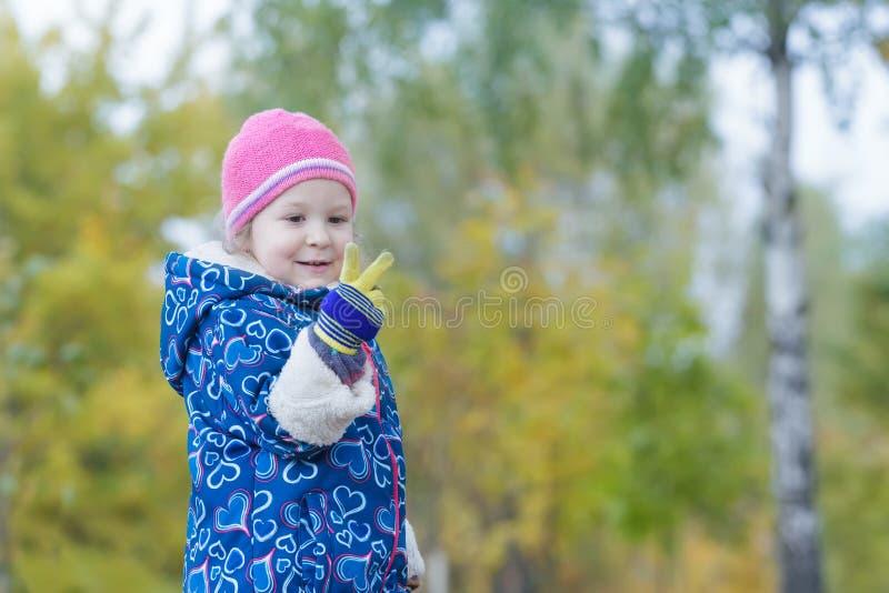 Dwa lat dziewczyna pokazuje dwa palca na jej ręce przy jesień parka ulistnienia tłem obraz royalty free
