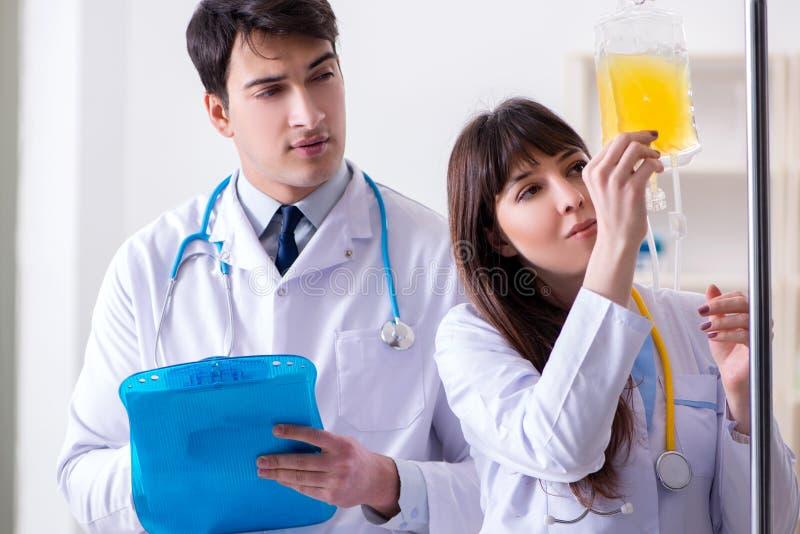 Dwa lekarki dyskutuje osocze i krwionośnego przetaczanie fotografia royalty free