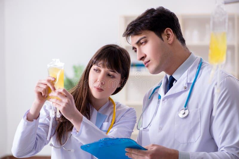 Dwa lekarki dyskutuje osocze i krwionośnego przetaczanie zdjęcia stock