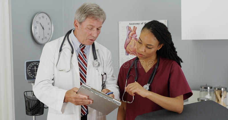 Dwa lekarki dyskutuje pacjentów rezultaty obrazy stock