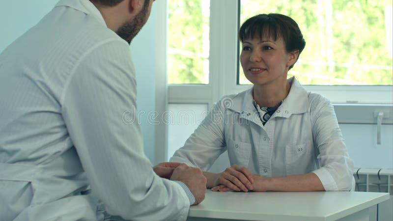 Dwa lekarki dyskutuje wpólnie i pracuje w medycznym biurze obrazy stock