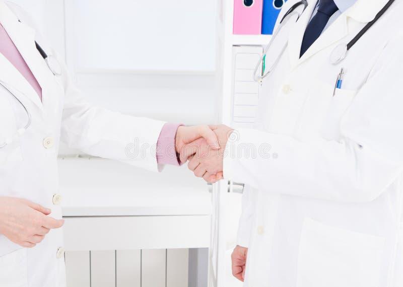 Dwa lekarki trząść ręki przy kliniką Ubezpieczenie Medyczne być pojęcia ręką opieki zdrowotnej pomoc opóźnioną pigułkę kosmos kop zdjęcia royalty free