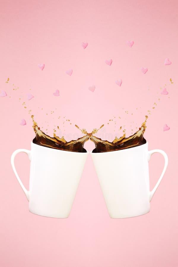 Dwa levitating kawowego kubka z pluśnięciami i serce confetti Cof obrazy royalty free