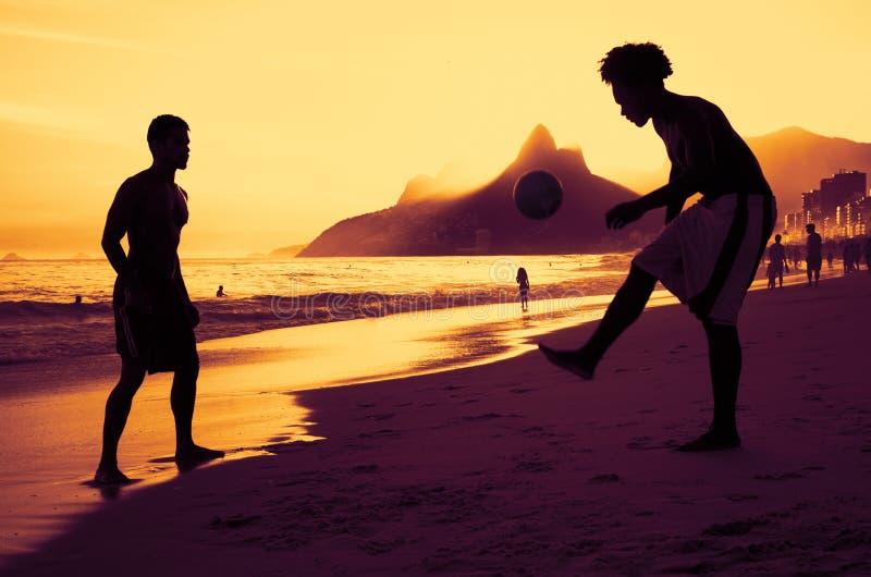 Dwa ludzie bawić się piłkę nożną przy plażą przy Rio przy zmierzchem fotografia royalty free
