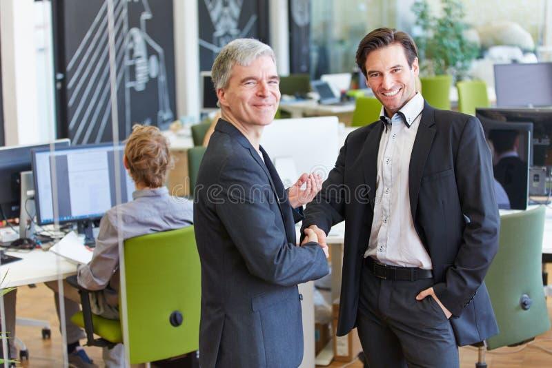 Dwa ludzie biznesu daje uściskowi dłoni w biurze obrazy stock