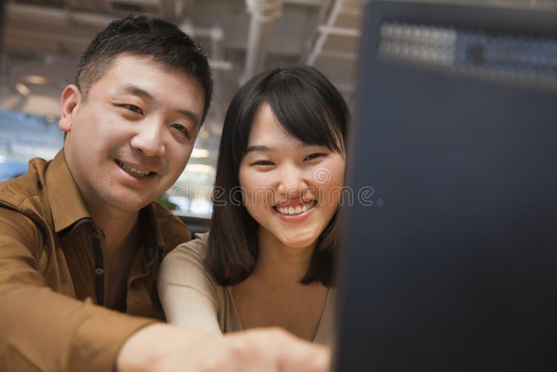 Dwa ludzie biznesu Patrzeje komputer w biurze zdjęcie royalty free