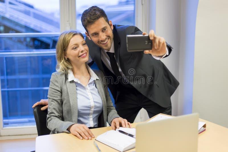 Dwa ludzie biznesu robi Selfie w biurze zdjęcia stock