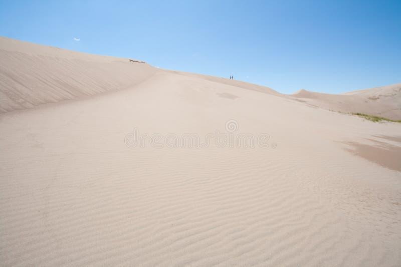 Dwa ludzie Chodzi przy Wielkim piasek diun parkiem narodowym w Kolorado zdjęcie stock