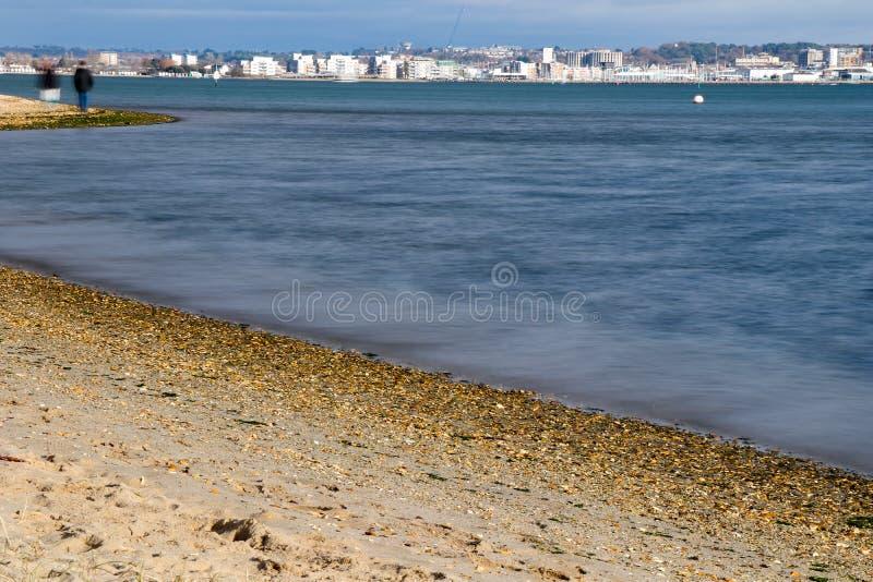 Dwa ludzie Chodzi Wzdłuż plaży z miastem na horyzoncie zdjęcia royalty free