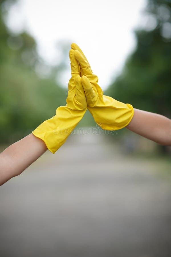 Dwa ludzie, jest ubranym lateksową rękawiczkę dla czyścić na ręce na asfaltowym tle Banialuki na tylnej stronie fotografia royalty free