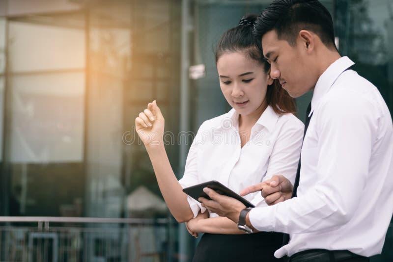 Dwa ludzie patrzeje smartphone i analizuje akcyjnych wykresy wewnątrz fotografia royalty free