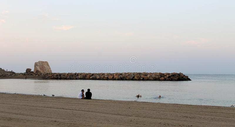 Dwa ludzie siedzi na piasku i opowiada bardzo zamkniętego each inny obok seashore zdjęcie royalty free