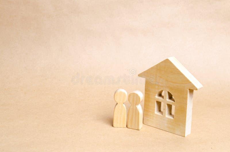 Dwa ludzie stoją blisko drewnianego domu Kilka młodzi ludzie stojaka blisko ich nowego domu Zakup i sprzedaż budynek mieszkalny A fotografia royalty free
