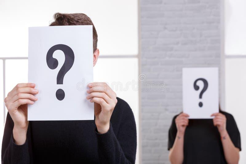 Dwa ludzie zakrywali ich twarze z znaka zapytania zakończeniem zdjęcia stock